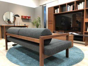 ウォルナット材で独特のシルエットを象りウォームグレーの配色で作られたソファ。