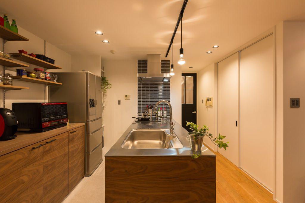 ウォルナットで組まれたキッチンとブラックのボーダータイルのコンビがカッコイイです。