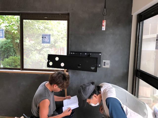 モールテックスで仕上げたお洒落な壁に、壁掛けテレビの金物を取り付ける大工さん