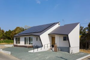 白いガルバにグレーの金属屋根。三角が特徴的な外観に青空が映えます。