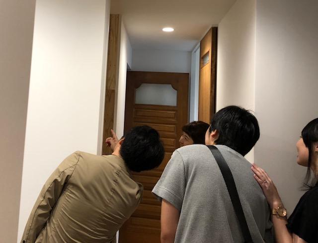 暮らしの見学。実家から移設したドアと、回遊動線のシューズクロークをのぞき込んでいます