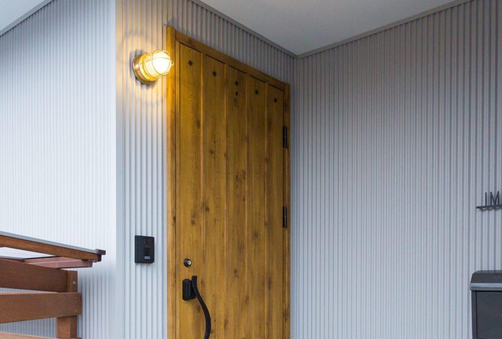 グレーの小波ガルバリウム鋼板と木目の玄関ドアに合います。