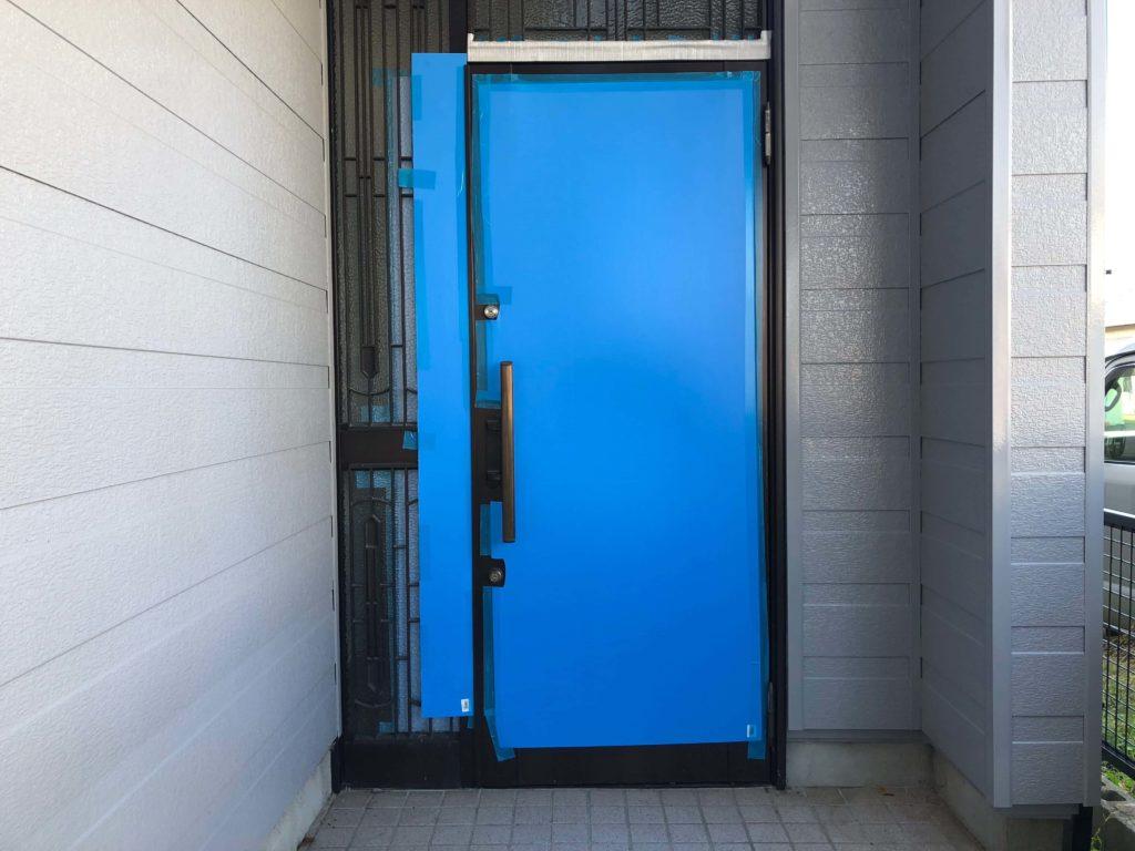 既設の玄関を活かすプランのため、ブルーの養生ボードで保全。無事にリノベーション工事が終わるようにとの思いです。