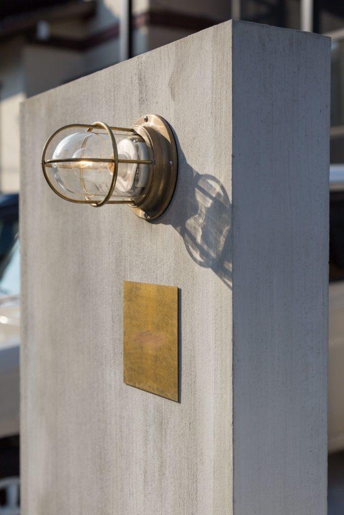ハケ引き仕上げのコンクリートの門柱にゴールドの船舶照明は相性抜群。