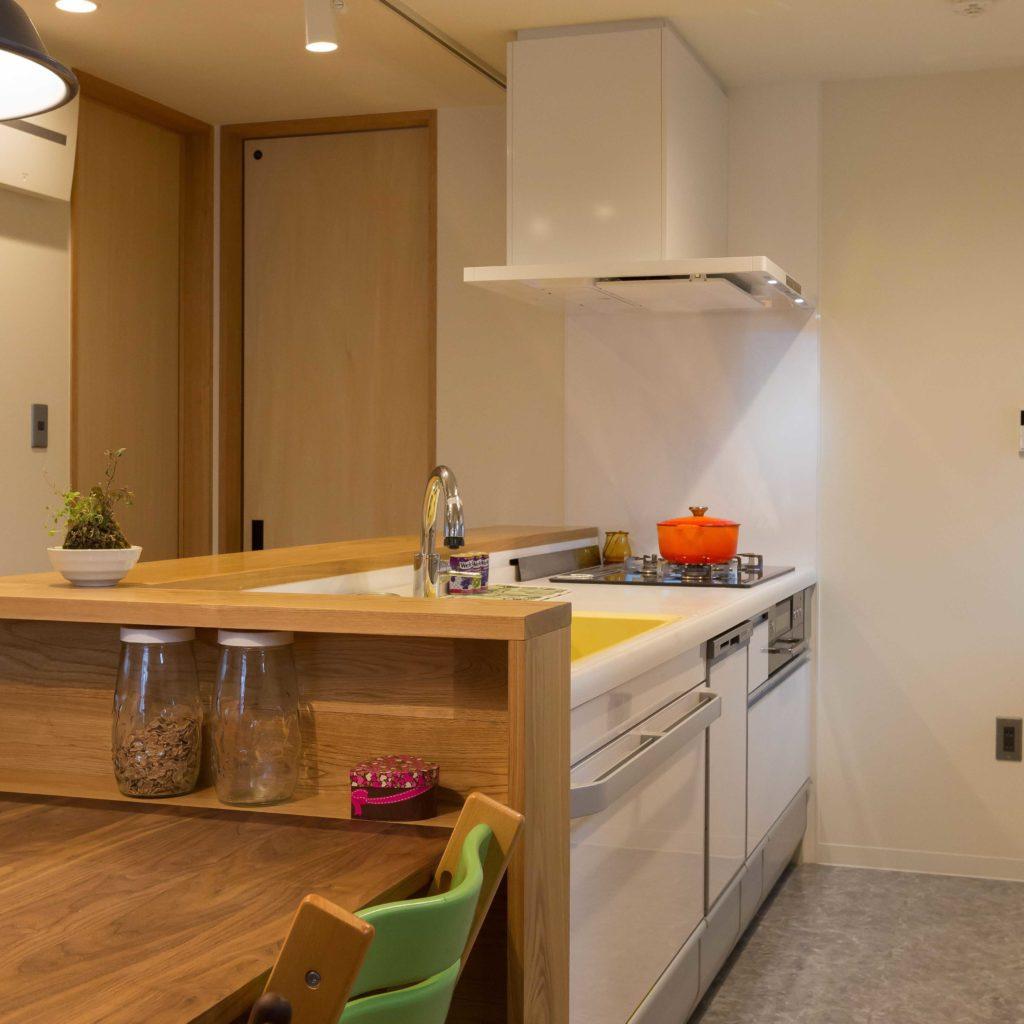 白を基調とした清潔感のあるキッチンに温かみのある無垢材の組み合わせ