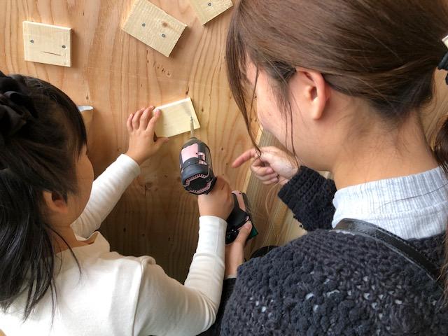 リノベーションエキスポでの職人体験、木を壁に打ち付ける作業です