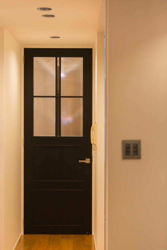 ブラックに塗装された背高のドア。両サイドの模様ガラスに対して中央だけクリアガラスを用いてます。