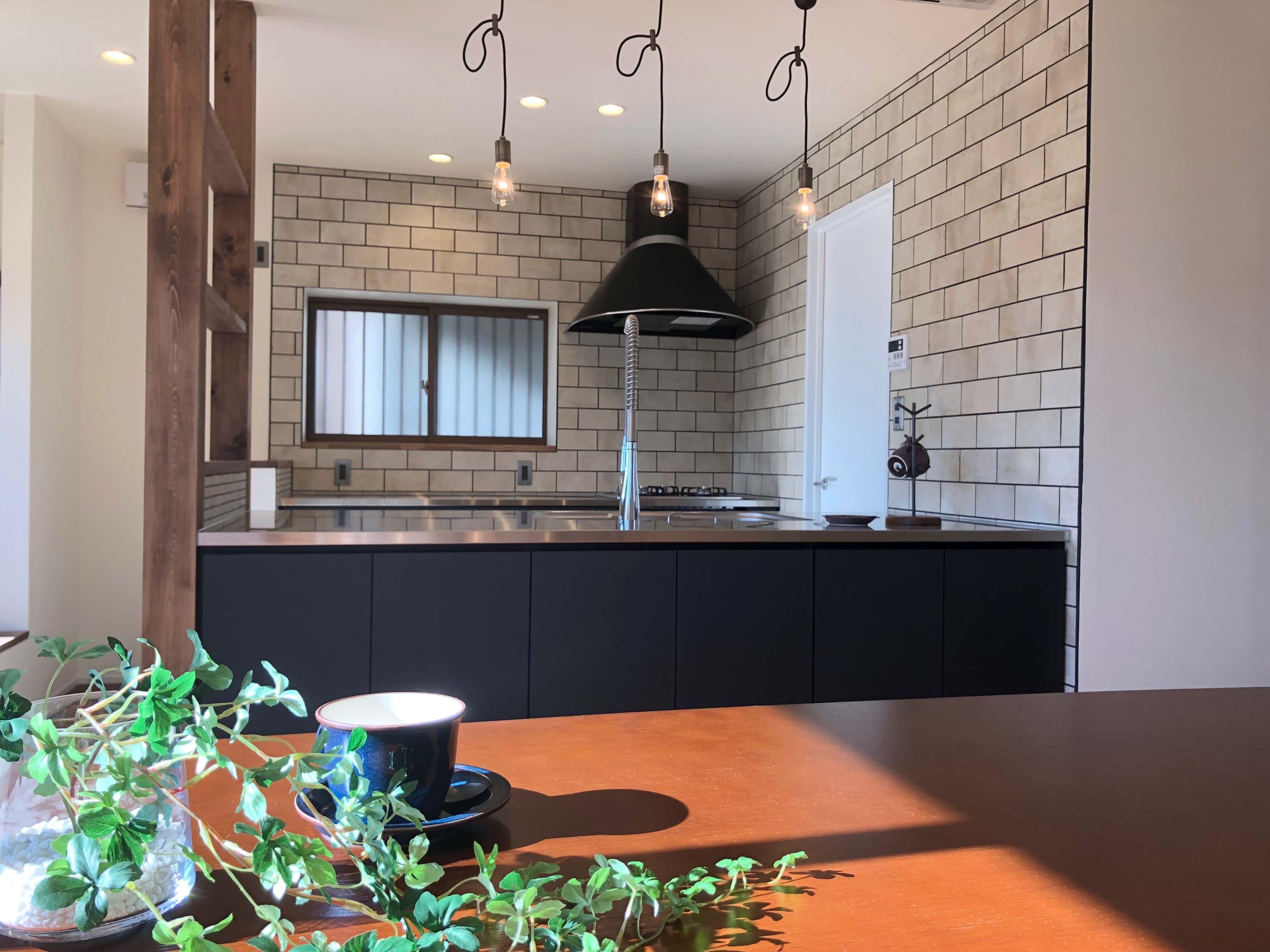ダークグレーのキッチンレトロテイストのタイル、ナラ材のテーブルにはカップとグリーン。暮らしの様子が感じられます。
