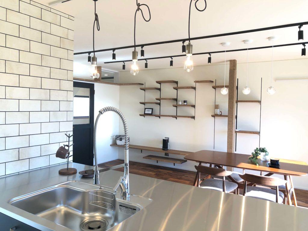 ステンレスカウンターから飾り棚やテレビボードが見え、家中の様子がキッチンからわかります。