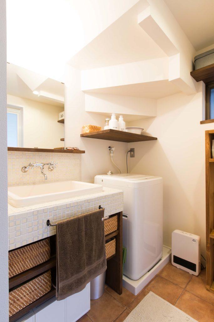 階段下の空間に洗濯機を設けている洗面脱衣室。レトロ感のあるタイルと実験流しの組み合わせがステキなんです。