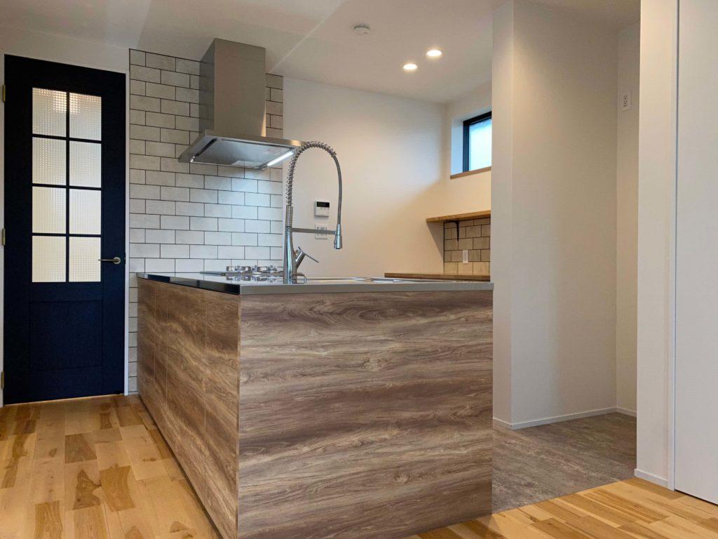 個性的なオリジナルキッチン、ダークネイビーのドア、白いレンガ模様のタイル。
