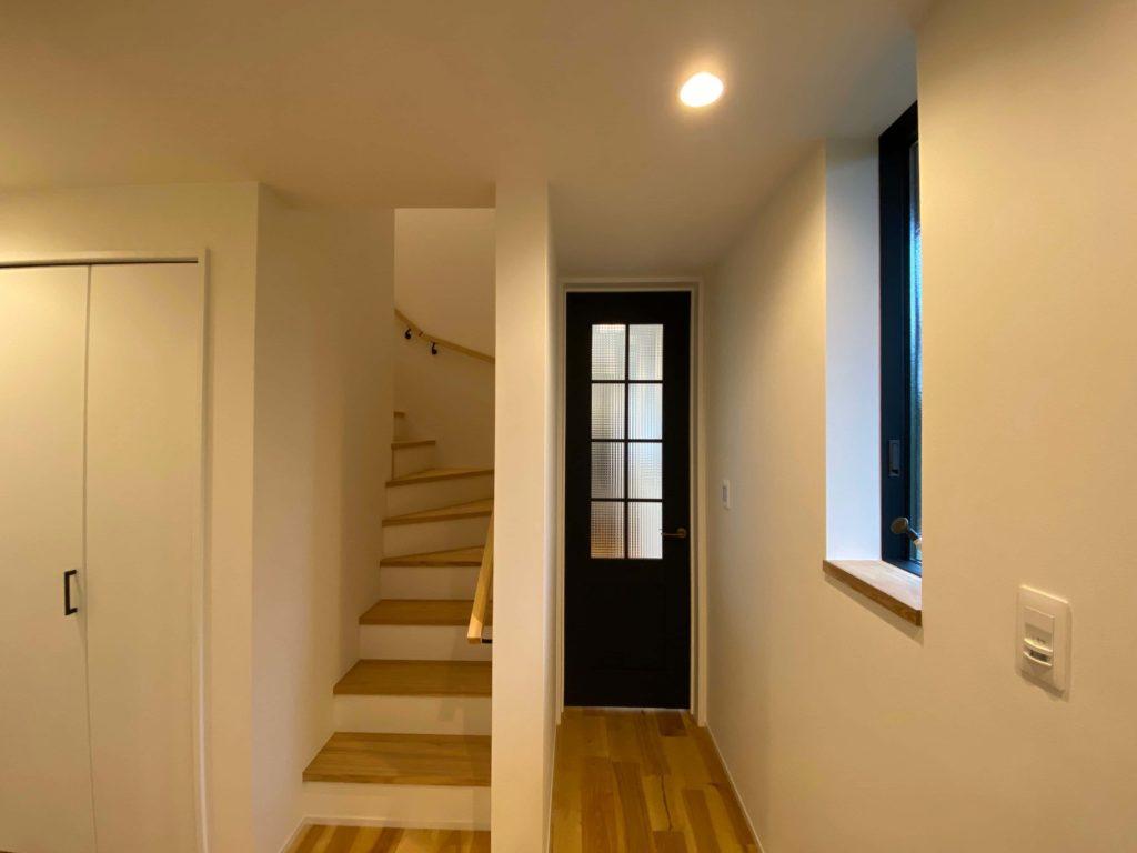 玄関ホールにリビングのドアと階段が並びます。