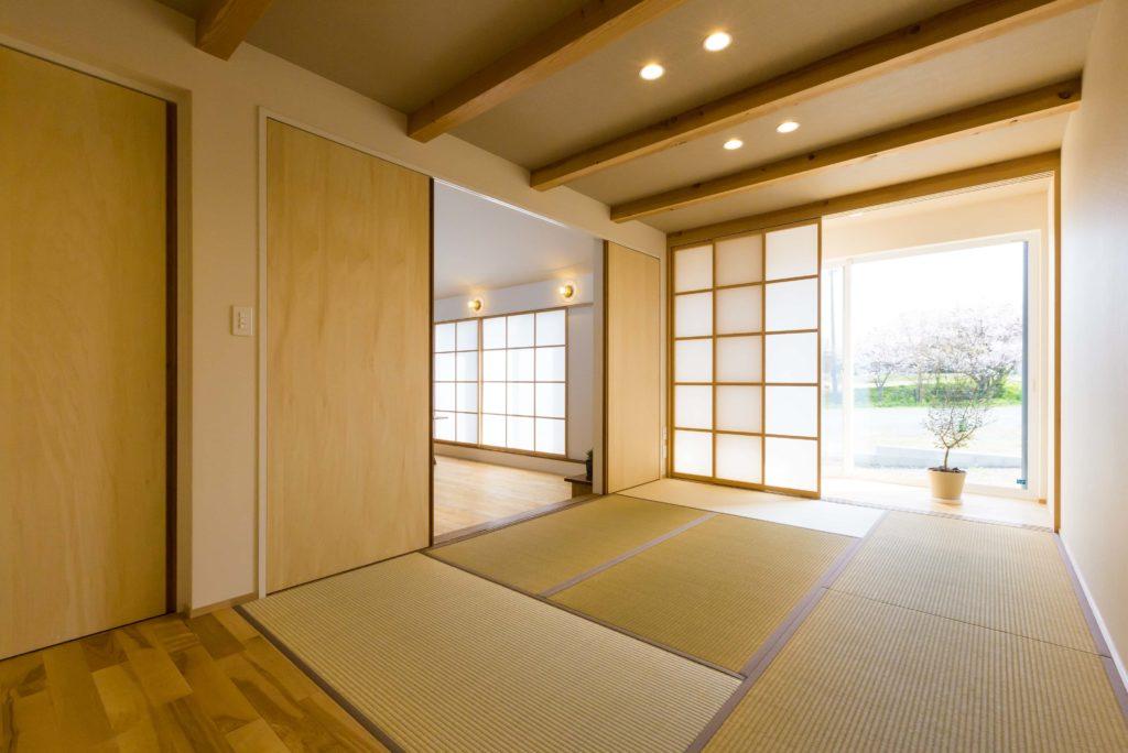 小上がりの和室に板畳と縁側。オリーブの植木が眩しい。