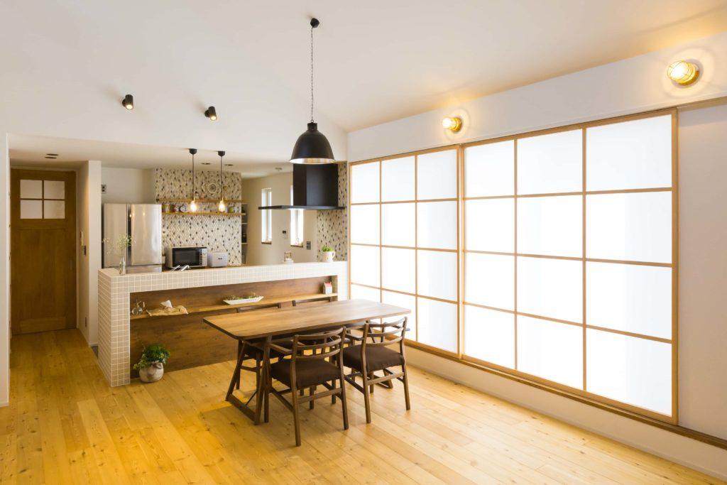 カラマツのフローリングとウォルナットのテーブル、大きな障子を組合わせたダイニングキッチン