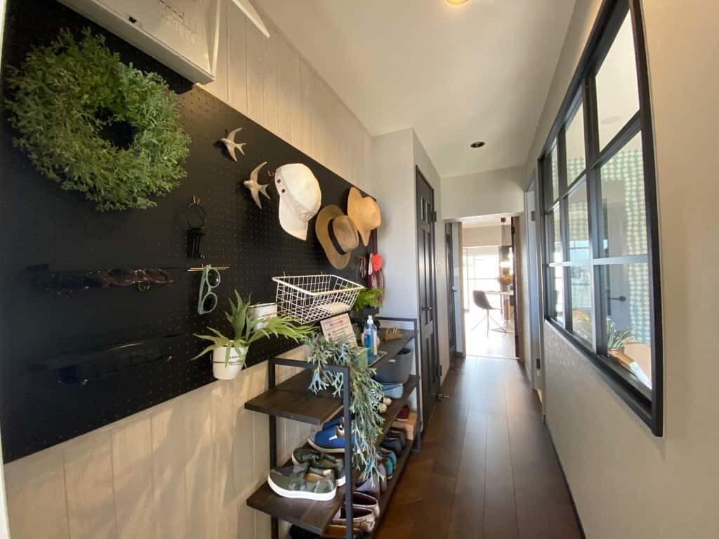 有孔ボードに思い思いのグッズが掛けられ、アイアンで作られたオープンな靴箱が楽しい玄関ホール。