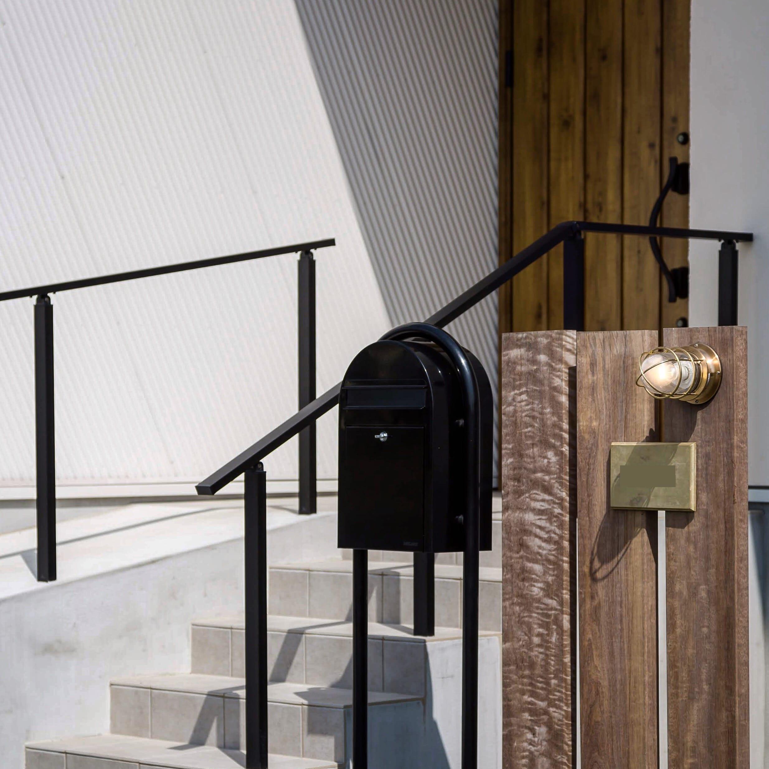 木材の茶色、ポストの黒、船舶照明・表札の真鍮の三色でまとめられたシンプルな門柱