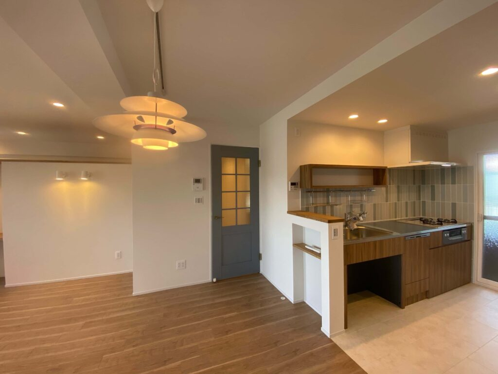 落ち着いた木目のオリジナルキッチンと優しい色目のタイルとドア。